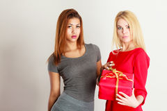 Δύο νέες κυρίες με το κόκκινο δώρο στοκ εικόνα