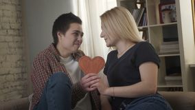 Δύο νέες λεσβίες χαριτωμένες εξετάζουν η μια την άλλη, που κρατά ένα σημάδι καρδιών στο χέρι τους 60 fps απόθεμα βίντεο