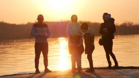 Δύο νέες οικογένειες με τα παιδιά που έχουν τη διασκέδαση κοντά στον ποταμό στο ηλιοβασίλεμα ενεργές νεολαίες ανθρώπ&o Υπαίθρια,  απόθεμα βίντεο