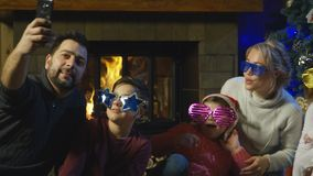 Δύο νέες οικογένειες που θέτουν για μια φωτογραφία Χριστουγέννων απόθεμα βίντεο