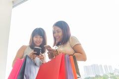 Δύο νέες συγκινημένες ασιατικές κυρίες που ψωνίζουν στο smartphone στοκ εικόνες