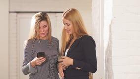 Δύο νέες φίλες με τη συνεδρίαση smartphone στον καφέ στην πόλη φιλμ μικρού μήκους