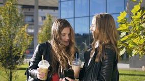 Δύο νέες χαμογελώντας γυναίκες που κοιτάζουν βιαστικά Διαδίκτυο στο κινητό τηλέφωνο περπατώντας σε ένα πάρκο της πόλης κοντά στο  απόθεμα βίντεο