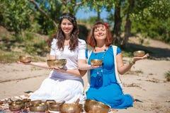 Δύο νέες όμορφες γυναίκες που παίζουν τα θιβετιανά τραγουδώντας κύπελλα στη φύση στην όχθη ποταμού Στοκ Εικόνα