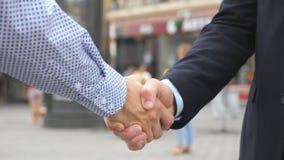 Δύο νέοι άνδρες συνάδελφοι που τινάζουν τα χέρια με το θολωμένο υπόβαθρο πόλεων Βέβαιοι επιχειρηματίες που χαιρετούν ο ένας τον ά φιλμ μικρού μήκους