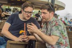 Δύο νέοι αρσενικοί φίλοι που έχουν τη διασκέδαση, που πίνουν τα κοκτέιλ και που κουβεντιάζουν με τους φίλους στον καφέ πεζουλιών  Στοκ φωτογραφία με δικαίωμα ελεύθερης χρήσης
