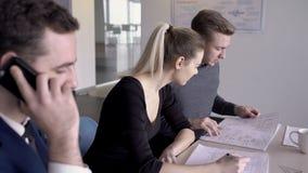 Δύο νέοι αρχιτέκτονες συζητούν το σχεδιάγραμμα οικοδόμησης και ο επιχειρηματίας μιλά στο συνεργάτη στο τηλέφωνο φιλμ μικρού μήκους
