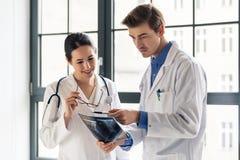 Δύο νέοι αφιερωμένοι γιατροί που αναλύουν μαζί μια ακτηνογραφία Στοκ εικόνες με δικαίωμα ελεύθερης χρήσης