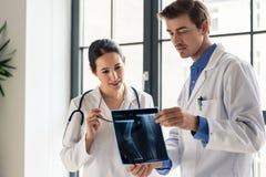 Δύο νέοι αφιερωμένοι γιατροί που αναλύουν μαζί την ακτηνογραφία ενός ασθενή Στοκ Εικόνα