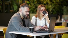 Δύο νέοι επαγγελματίες που κάθονται στο γραφείο, που εξετάζουν την οθόνη lap-top και που συζητούν το πρόγραμμα από κοινού Το κορί φιλμ μικρού μήκους