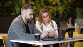 Δύο νέοι επαγγελματίες που κάθονται στο γραφείο, που εξετάζουν την οθό φιλμ μικρού μήκους
