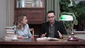 Δύο νέοι επιστήμονες που έχουν τη συνεδρίαση καταιγισμού ιδεών στον πίνακα με ένα ανοιγμένο βιβλίο φιλμ μικρού μήκους