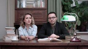 Δύο νέοι επιστήμονες που κάθονται στο γραφείο που παρουσιάζει το πρόγραμμά τους απόθεμα βίντεο