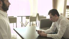 Δύο νέοι επιχειρηματίες επικοινωνούν σε έναν καφέ Χειρωνακτικός πυροβολισμός απόθεμα βίντεο