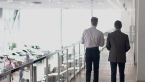 Δύο νέοι επιχειρηματίες που περπατούν μέσω της στοάς στο κέντρο αυτοκινήτου, σε αργή κίνηση φιλμ μικρού μήκους