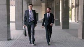 Δύο νέοι επιχειρηματίες που περπατούν στο γραφείο από κοινού απόθεμα βίντεο