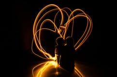 Δύο νέοι εραστές χρωματίζουν μια καρδιά στην πυρκαγιά Σκιαγραφία των λέξεων ζευγών και αγάπης σε ένα σκοτεινό υπόβαθρο Στοκ Εικόνες