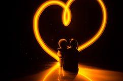 Δύο νέοι εραστές χρωματίζουν μια καρδιά στην πυρκαγιά Σκιαγραφία των λέξεων ζευγών και αγάπης σε ένα σκοτεινό υπόβαθρο Στοκ φωτογραφίες με δικαίωμα ελεύθερης χρήσης