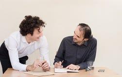 Δύο νέοι ευτυχείς καυκάσιοι συνάδελφοι στον πίνακα στο γραφείο με το ελαφρύ υπόβαθρο στοκ εικόνα
