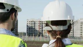 Δύο νέοι μηχανικοί ένας άνδρας και μια γυναίκα στις πράσινα φανέλλες και τα κράνη απόθεμα βίντεο