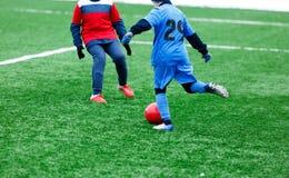 Δύο νέοι ποδοσφαιριστές στο κόκκινο και μπλε sportswear τρέξιμο, dribble και τον ανταγωνισμό για τη σφαίρα Κατώτερος ανταγωνισμός στοκ φωτογραφία