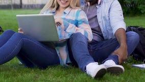 Δύο νέοι που κάθονται στη χλόη, κορίτσι που κλίνει στον τύπο και που κρατά το lap-top απόθεμα βίντεο