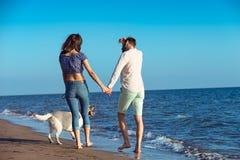 Δύο νέοι που τρέχουν στην παραλία που φιλά και που κρατά σφιχτά με το σκυλί Στοκ φωτογραφίες με δικαίωμα ελεύθερης χρήσης