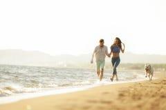 Δύο νέοι που τρέχουν στην παραλία που φιλά και που κρατά σφιχτά με το σκυλί Στοκ Φωτογραφία