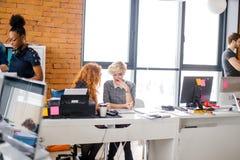 Δύο νέοι συνάδελφοι κουτσομπολεύουν αντίστροφο στα μουρμουρίσματα ανεμιστήρας το αεράκι στοκ εικόνα με δικαίωμα ελεύθερης χρήσης