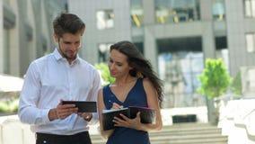 Δύο νέοι συνέταιροι που εργάζονται στην οδό Συνέταιροι που συζητούν τα έγγραφα και τις ιδέες, που στέκονται μπροστά από Στοκ εικόνα με δικαίωμα ελεύθερης χρήσης