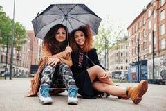 Δύο νέοι φίλοι που κάθονται skateboard με μια ομπρέλα Στοκ Εικόνες
