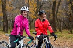 Δύο νέοι χαμογελώντας θηλυκοί ποδηλάτες με τα οδικά ποδήλατα που στηρίζονται και στο πάρκο στην κρύα ημέρα φθινοπώρου Υγιής τρόπο Στοκ εικόνες με δικαίωμα ελεύθερης χρήσης