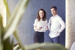 Δύο νέος άνδρας γυναικών επαγγελματιών ή σπουδαστών ευχαριστημένος από την επιχειρησιακή συνεδρίαση, που χαμογελά και που μιλά γι Στοκ Φωτογραφία
