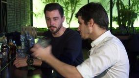 Δύο νεαροί άνδρες που απολαμβάνουν να πιει μαζί στο φραγμό μετά από την εργάσιμη ημέρα απόθεμα βίντεο