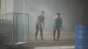 Δύο νεαροί άνδρες που χορεύουν στο σκοτεινό και σκονισμένο δωμάτιο του εγκαταλειμμένου κτηρίου Φίλοι που ασκούν στον σπάσιμο-χορό απόθεμα βίντεο