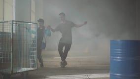 Δύο νεαροί άνδρες που χορεύουν στο σκοτεινό και σκονισμένο δωμάτιο του εγκαταλειμμένου κτηρίου Έφηβοι που κάνουν την κίνηση χορού απόθεμα βίντεο