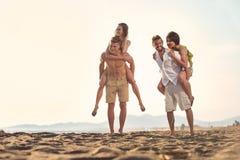 Δύο νεαροί άνδρες που δίνουν τις φίλες τους piggyback οι γύροι στην παραλία στοκ εικόνα