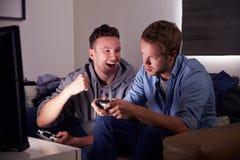Δύο νεαροί άνδρες που παίζουν το τηλεοπτικό παιχνίδι στο σπίτι στοκ φωτογραφία