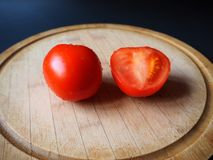Δύο ντομάτες στο στρογγυλό ξύλινο τέμνοντα πίνακα στοκ φωτογραφίες