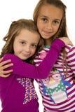 Δύο ξάδελφοι κοριτσιών που φορούν τις πυτζάμες Χριστουγέννων που αγκαλιάζουν η μια την άλλη στοκ φωτογραφίες με δικαίωμα ελεύθερης χρήσης