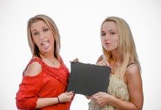 Δύο ξανθά κορίτσια που κρατούν τον κενό πίνακα κιμωλίας Στοκ Εικόνα
