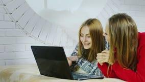 Δύο ξανθά κορίτσια προσέχουν ένα αστείο βίντεο στο lap-top και βρίσκονται στο κρεβάτι απόθεμα βίντεο