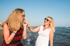 Δύο ξανθά κορίτσια στην παραλία κοντά στη θάλασσα Στοκ Φωτογραφίες