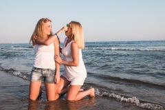 Δύο ξανθά κορίτσια στην παραλία κοντά στη θάλασσα Στοκ Εικόνες