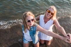 Δύο ξανθά κορίτσια στην παραλία κοντά στη θάλασσα Στοκ Εικόνα