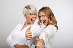 Δύο ξανθές γυναίκες που χαμογελούν φυλλομετρούν επάνω Στοκ Εικόνες