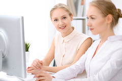 Δύο ξανθές επιχειρησιακές γυναίκες που κάθονται στο γραφείο στην αρχή Στοκ εικόνες με δικαίωμα ελεύθερης χρήσης
