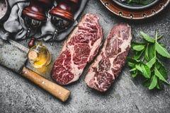 Δύο ξηρές ηλικίας ακατέργαστες μπριζόλες βόειου κρέατος με τον μπαλτά και το καρύκευμα κρέατος στο σκοτεινό αγροτικό συγκεκριμένο στοκ εικόνες με δικαίωμα ελεύθερης χρήσης