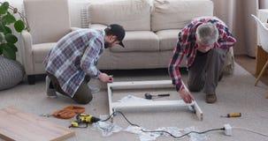 Δύο ξυλουργοί που συγκεντρώνουν τα έπιπλα στο σπίτι απόθεμα βίντεο