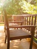 Δύο ξύλινες καρέκλες και ένας πίνακας στο μπαλκόνι το καλοκαίρι με το φυσικό υπόβαθρο δέντρων Στοκ Εικόνες